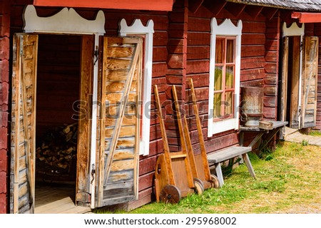 Open storage sheds and old carts and benches outside.