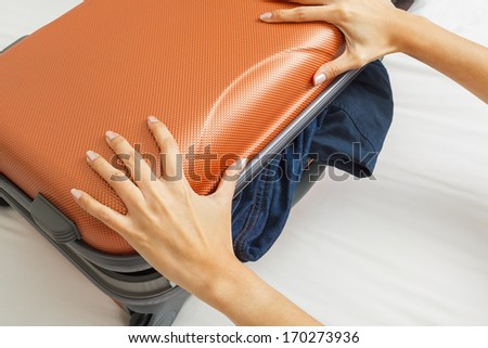 open suitcase with clothes on bed - stock photo