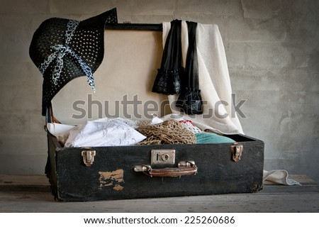 Open suitcase with old things on the brick wall background