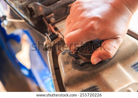 Open the fuel cap,Hand opening the oil filler cap - stock photo