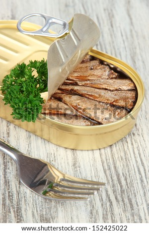 Open tin can with sardines, on wooden background - stock photo
