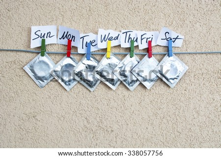 open (used) condom and sealed condoms on colorful clothespins. seven days of the week - sexweek, space for text - stock photo
