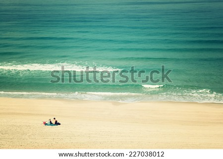 open view to beach shore and sea waves and lonely couple sitting looking at the horizon. - stock photo