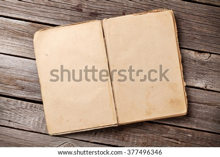 Open vintage book on wooden background. Top view with copy space - stock photo