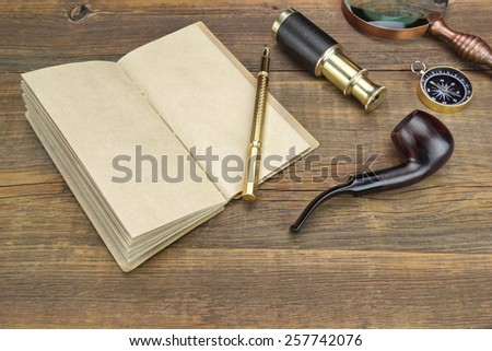 Open Vintage Notebook With Blank Pages, Gold Fountain Pen, Retro Magnifier, Compass and Spyglass On Grunge Wooden Table Background