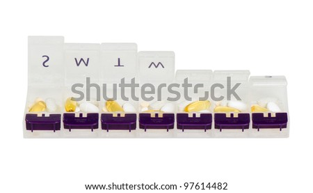 Open weekly pill organizer filled with pills - stock photo