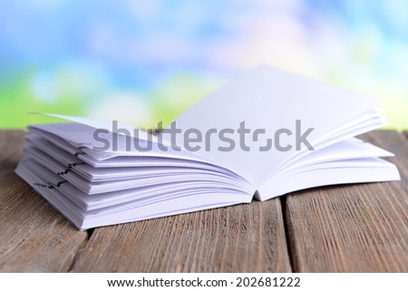 Open white book on wooden table on bright background
