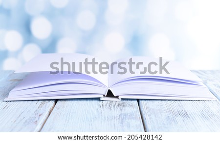 Open white book on wooden table on bright background - stock photo