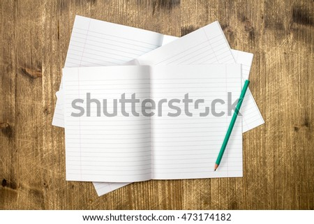 Open white lined exercise books and pencil on wooden table