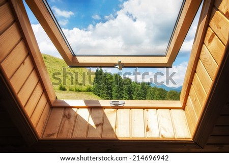 Open window at village wooden house in mountains. Amazing view of summer landscape with forest and meadow under blue sky  - stock photo