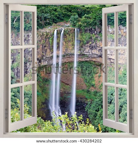 Open window view to the highest waterfall on Mauritius, Chamarel Waterfall,  plunges more than 85 meters down against a scenic backdrop of forests and mountains - stock photo