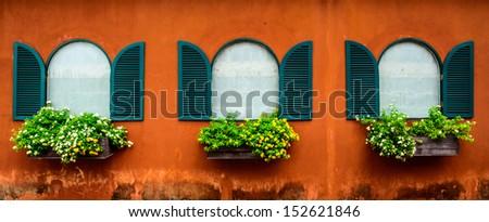 Open Window With Flower Basket On Orange Wall - stock photo