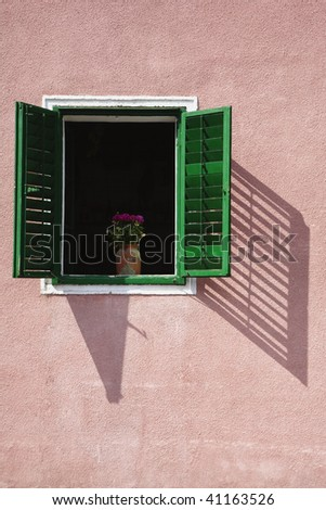 Open window with flower vase with green shutters located in a Zagreb neighborhood. - stock photo