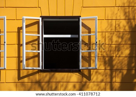 open window with white frames, yellow bricks and some shadows