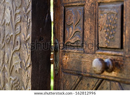 Open wooden door with carved floral  patterns - stock photo