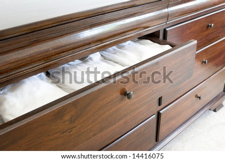 open wooden dresser drawer with white clothing