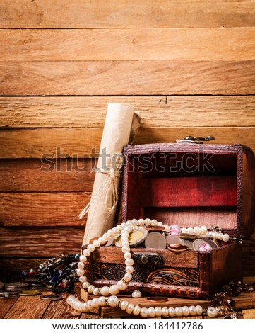 Open wooden treasure chest with valuables on wooden background - stock photo