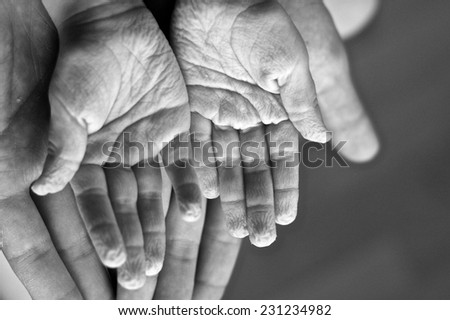 Open wrinkled hands of a child on adult's hands, monochrome - stock photo