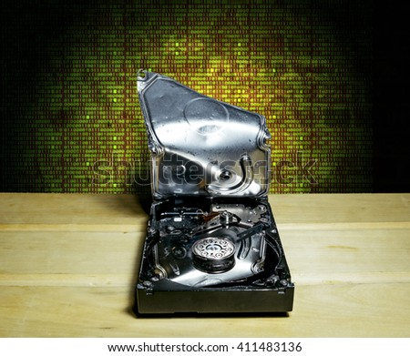 Opened and broken the hard drive from the computer in the background of the digits of the matrix - stock photo