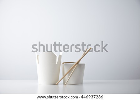 Opened and closed takeaway boxes for chinese noodles presented with chopsticks, isolated on white Retail set - stock photo