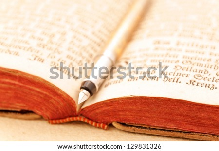 Opened antique book with fountain pen - stock photo