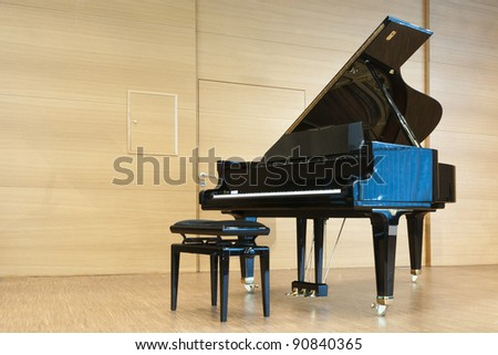 opened black grand piano with stool on a wooden concert stage - stock photo