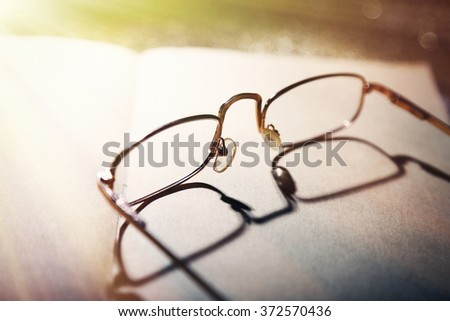 Opened book and eyeglasses on it, close up - stock photo
