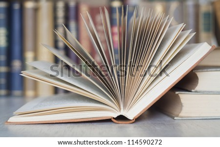 opened book close up with bookshelf in the back, selective focus - stock photo