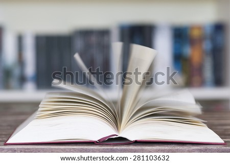 Opened book in front of bookcase with flying pages and motion blur with selective focus.