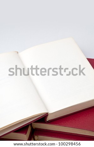 Opened book lying on other books, close up - stock photo