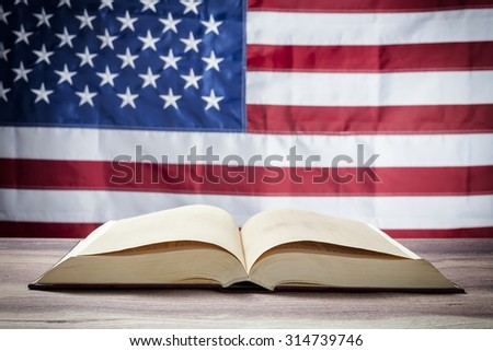 Opened book on a background of the USA flag - stock photo