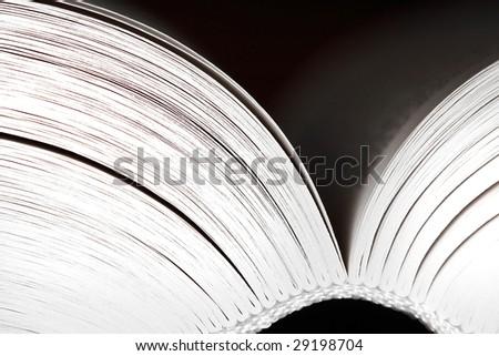 Opened book on dark background - black and white - stock photo