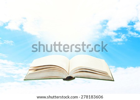 Opened book on sky background - stock photo