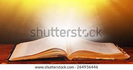 Opened book on table on brown background - stock photo