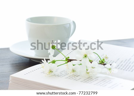 opened book with cherry blossom on with white cup on the background - stock photo