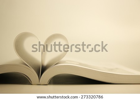 Opened book with heart page against blank background. - stock photo