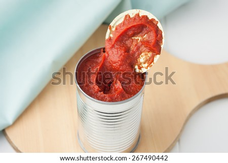 opened can of tomato paste on wooden round cutting board - stock photo