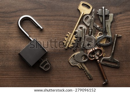 opened check-lock and different keys on wooden background concept - stock photo