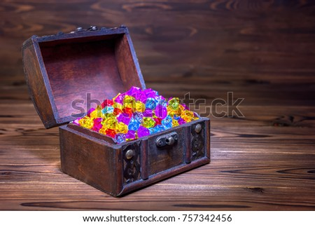 opened chest treasure with jewel decoration over wooden background, close up