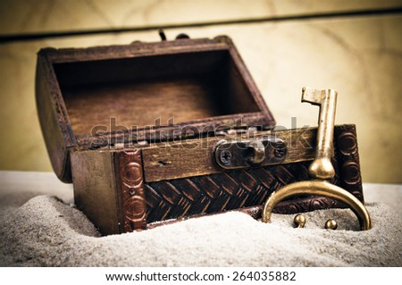 Opened decorative treasure chest with old metal key in the sand - stock photo