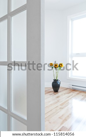 Opened door leading into a contemporary room full of light, decorated with flowers. - stock photo
