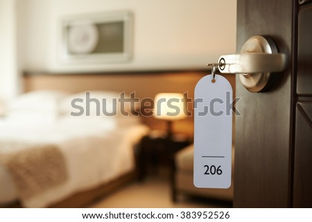 Opened door of hotel room with key in the lock - stock photo