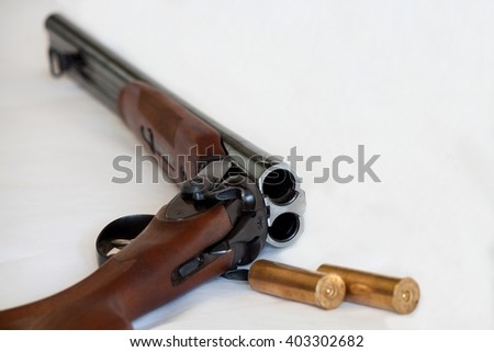 Opened double-barrelled gun with two bullets close-up photo isolated on white background - stock photo