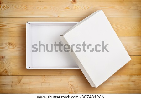 Opened empty cardboard box with cover on wooden background. - stock photo