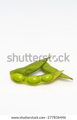 Opened fresh boiled green Japanese bean on white background - stock photo