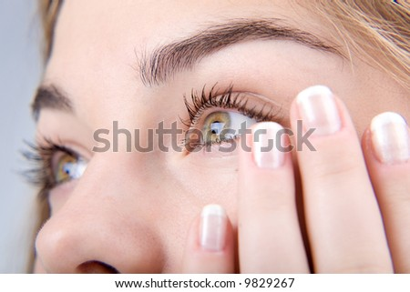 Opened green eyes and fingernails with french manicure close-up - stock photo