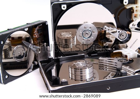 Opened hard drives, mirrored in plates, isolated on white background