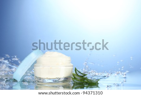 Opened jar of cream in water splashes on blue background - stock photo