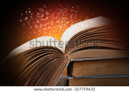 Opened magic book on abstract red gold background  - stock photo