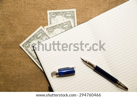 Opened notebook with a blank sheet, pen and money on the old tissue - stock photo
